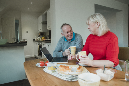 Mature couple are socialising over lunch and a cup of tea at home.