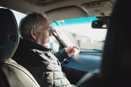 Senior man is sitting in the passenger seat of a car, talking to the driver who cannot be seen in the frame.