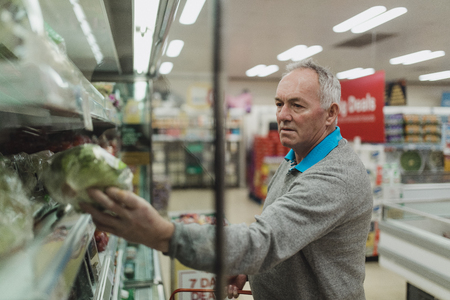 Senior man is buying fruit and vegetables in a supermarket.