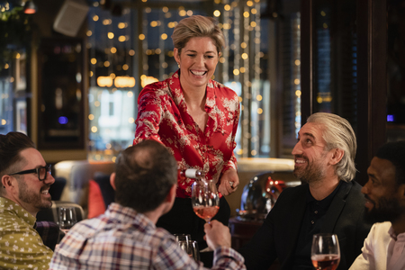 Female waitress standing at the edge of the table as she pours a glass of rose wine for a mature adult man. Stock Photo