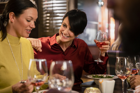 Two mature women enjoying a glass of rose wine with their meal. They are laughing and smiling while talking. Stock Photo