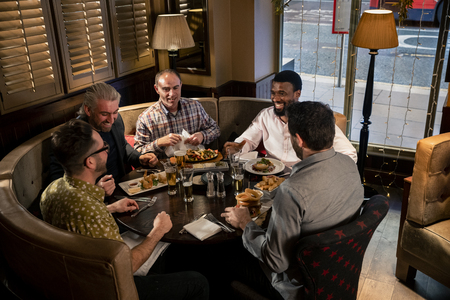 Group of mature men sitting at the table in a restaurant. They are enjoying food, talking and laughing.