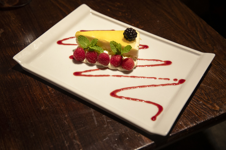 Slice of lemon cheesecake on a plate. It has been garnsihed with a blackberry and raspberries.