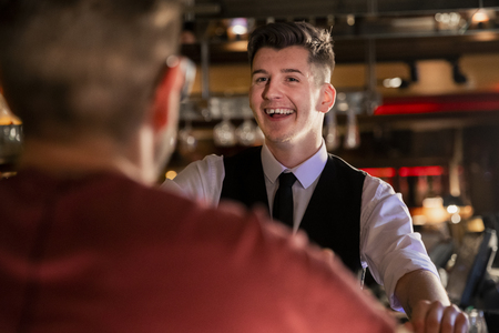 Over the shoulder view of a young male bartender who is laughing and talking with a customer at the bar. Stock Photo