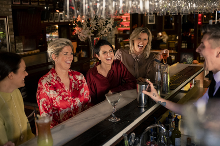 Small group of mature women enjoying a night, sitting at the bar. They are laughing with the young bartender who is making a cocktail.