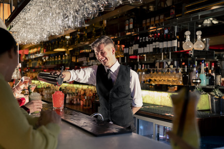 Young bartender pouring a cocktail out of a coktail shaker at the bar counter. Stock Photo