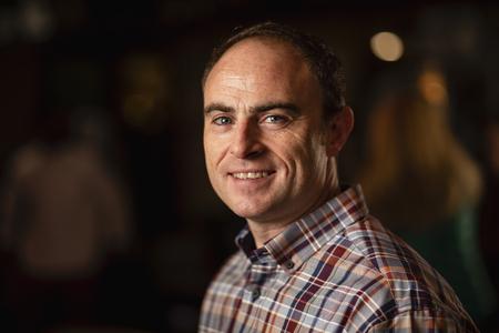 Headshot of a mature man smiling and looking at the camera.