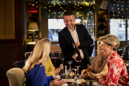 Mature waiter reccomending a bottle of champagne to a small group of mature women. They are sitting at a table in a restaurant. Stock Photo