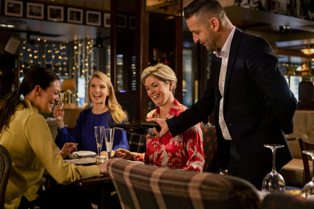 Mature waiter pouring a glass of prosecco for a table with three mature women sitting, laughing and smiling.