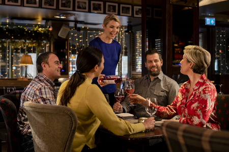 Two couples sitting at a table in a restaurant. The waitress is pouring a glass of while while a mature female holds the glass.