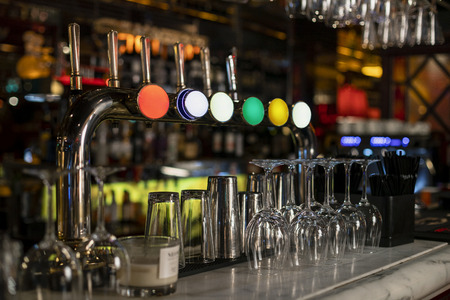Close-up of a row of beer taps on a bar counter in a restaurant.