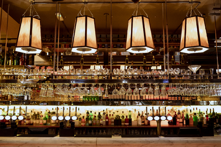 Wide angle shot of a restaurant interior of the bar counter and shelves of alcohol behind the bar. Stock Photo