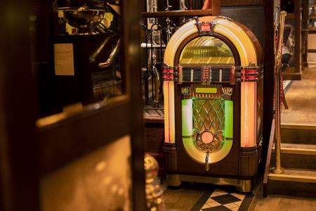 Retro jukebox in de hoek van een restaurant bij een trap.