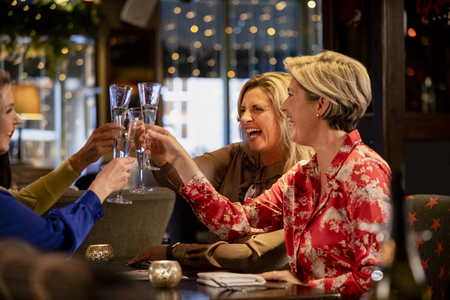Small group of mature female friends making a celebratory toast while sitting around a table in a restaurant. Reklamní fotografie