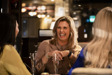 Over the shoulder view of a mature woman laughing and smiling with her friends while sitting in a restaurant. Reklamní fotografie