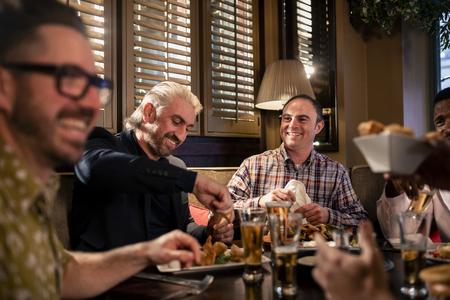 Small group of mid adult men enjoying some food in a restaurant. Reklamní fotografie