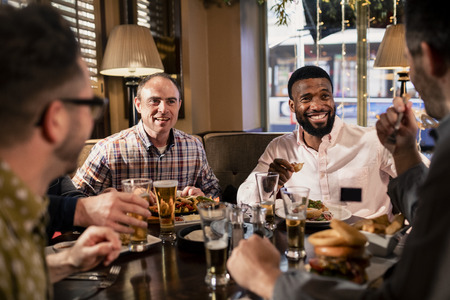 Small group of mid adult male friends enjoying some food in a restaurant. They are talking and enjoying each others company. Reklamní fotografie