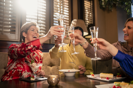 Small group of mature female friends making a celebratory toast while sitting around a table in a restaurant. Stock Photo