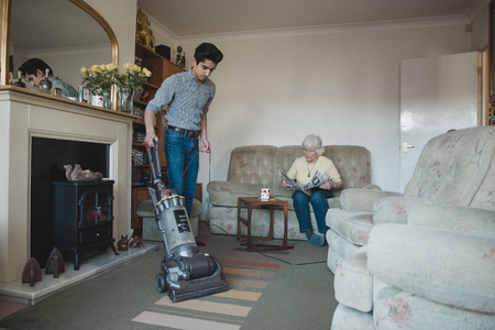 Teenage boy is hoovering his grandmothers living room for her while she reads a newspaper.