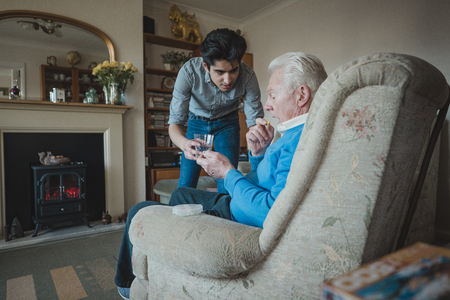 Teenage boy is giving his grandfather his medication.