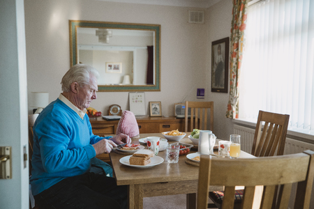 One senior man is sitting at the dining table in his home having lunch. He is making a ham salad sandwich.
