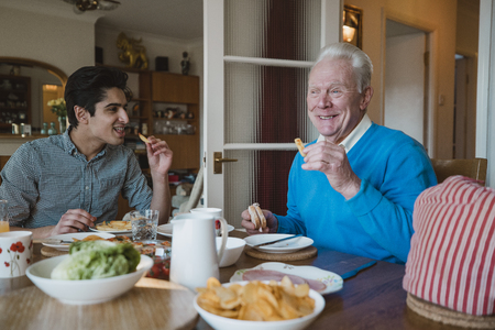 Senior man is having lunch at home with his grandson. They are eating sandwiches and potato chips.