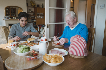 Senior man is having lunch at home with his grandson. They are eating sandwiches, pizza and potato chips.