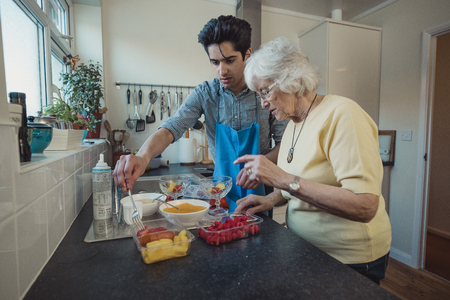 Teenage boy making fruit compote with his grandmother in the kitchen of her home.