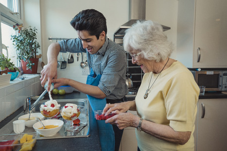 Teenage boy making fruit compote with his grandmother in the kitchen of her home. He is adding squirty cream to the bowls.