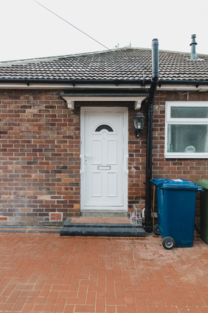 Shot of a front door on a bungalow with bins and milk bottles. Фото со стока
