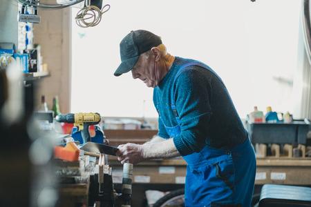 Senior man is sawing wood in his workshop.