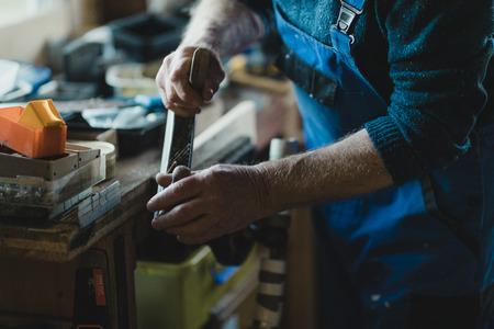 Close up shot of a senior man using a surform planer on wood in his workshop.