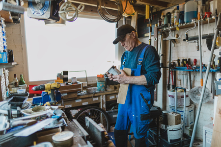 Senior man is working in his shed and is reading the label on a varnish.