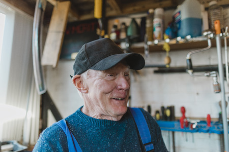 Close up headshot of a senior man in his workshop.