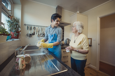 Teenage boy is talking to his grandmother while he washes the dishes in her kitchen.