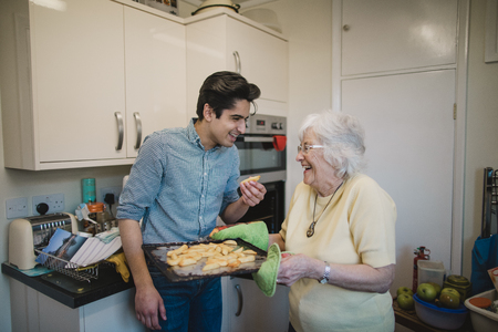 Teenage boy and his grandmother are laughing in the kitchen together after the teenager has taken a potato chip from the tray his grandmother has removed from the oven. Stock Photo
