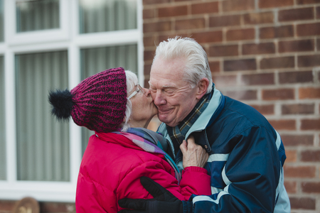 Senior woman is kissing her husband outside of their home in the winter.