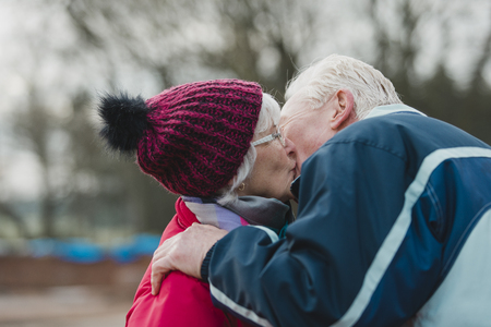 Senior man is kissing his wife outside of their home in the winter.