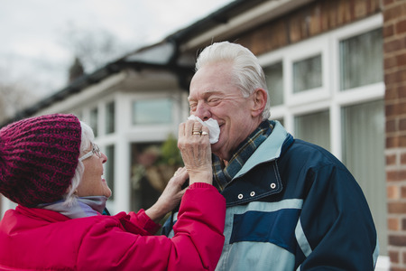 Senior woman is wiping her husbands nose while they are outside in the cold. Stock Photo