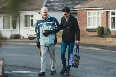 Teenage boy is walking back from the shop with his grandparent. He is carrying the shopping bag and they are linking arms.