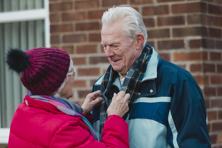 Senior woman is putting a scarf on hier husband in their front yard before they leave to go out in the cold. Reklamní fotografie