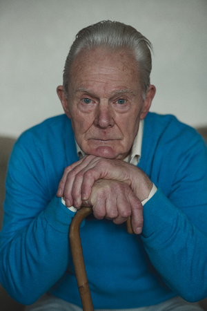 Portrait of a senior man looking sad while leaning on his walking stick. Stock Photo