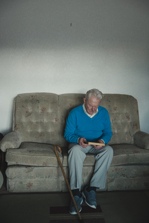 Senior man is sitting alone in the living room of his home, looking at an old photo. Stock Photo