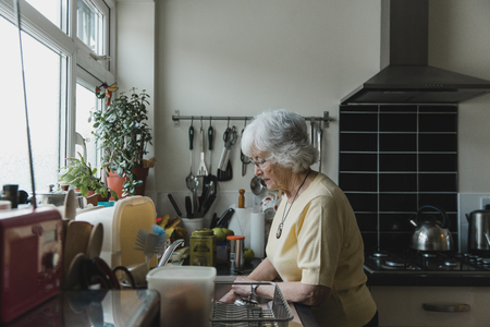 Senior woman is washing dishes in the kitchen of her home.