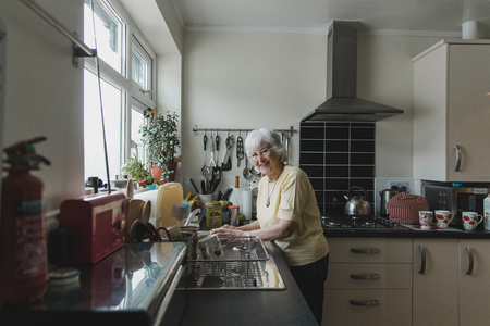 Senior woman is smiling for the camera while washing dishes in the kitchen of her home. Reklamní fotografie