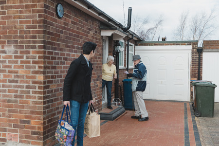 Teenager and his grandfather are leaving to go shopping together. The grandmother is standing in the doorway of their home and is giving her husband a shopping list. Reklamní fotografie