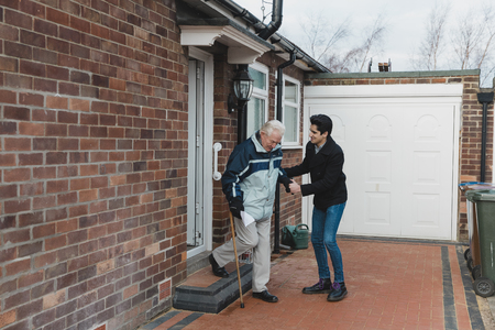 Teenage boy is helping his grandfather out of the door and down the steps of his house.