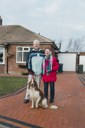 Portrait of a senior couple and their pet dog in the front yard of their house. Reklamní fotografie