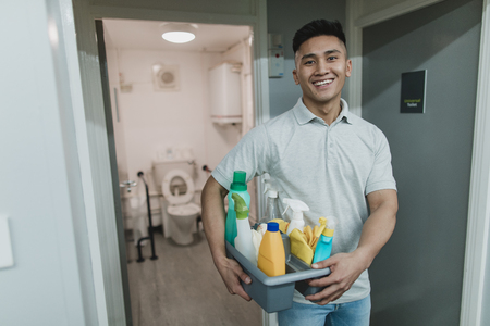 Portrait of a young, male cleaner at work. He is holding a tray of cleaning products.
