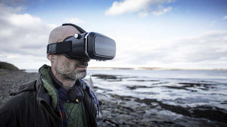 A front-view shot of a mature caucasian man wearing a virtual reality headset while standing on a beach in the United Kingdom, he is having fun.